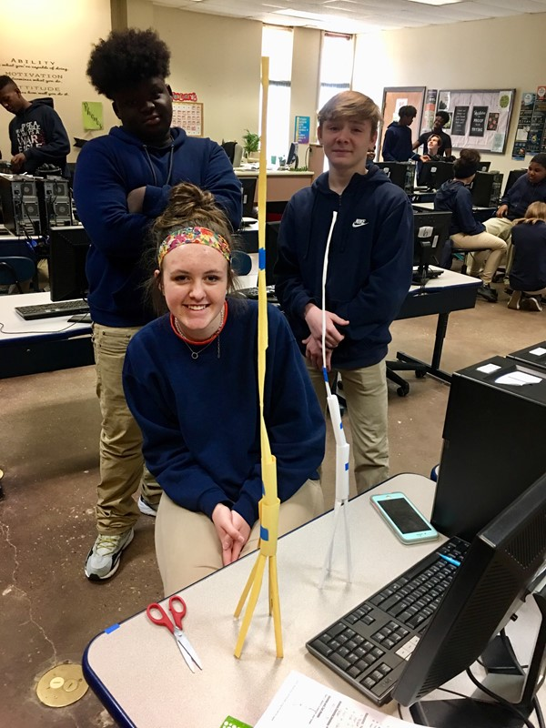 Mrs. Malone's STEM class implementing the engineering design process while creating a tower from one sheet of paper and one foot of tape.